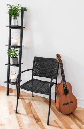 Room with simple black furniture, plants and classical guitar  Foto de archivo