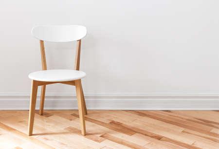 Silla blanca elegante en una habitación vacía, con suelo de madera.