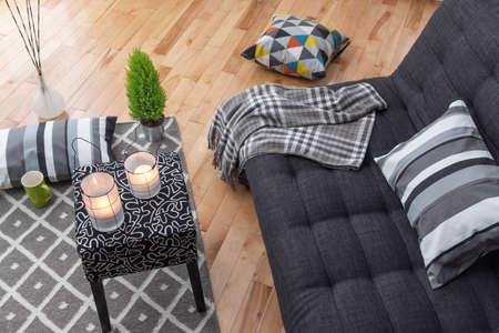 Detail van een lichte moderne woonkamer met grijze bank. Stockfoto