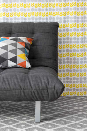 Sofa with colorful cushion, on bright floral background  Foto de archivo