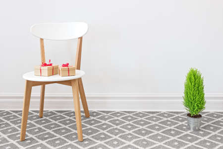 Presents on an elegant white chair, and little green cypress tree