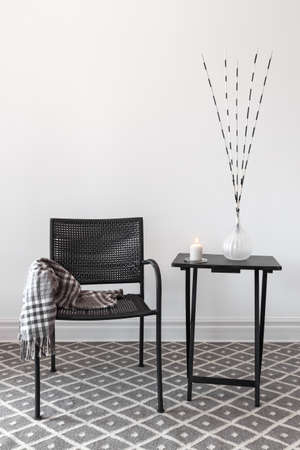 Home decor  Black armchair and little table decorated with decorations  Foto de archivo