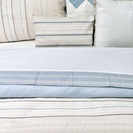 Bed with elegant blue bed linen and pillows.