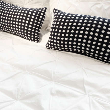 Bed with white bed linen and black polka dot cushions