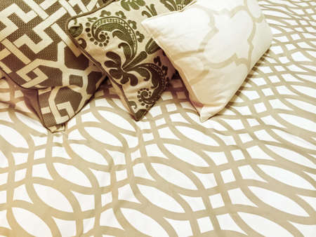 Close-up of a bed with three decorative cushions