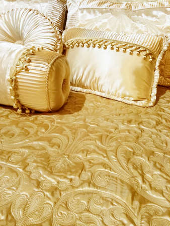 Bed with luxurious silky bedding and decorative cushions. Stockfoto