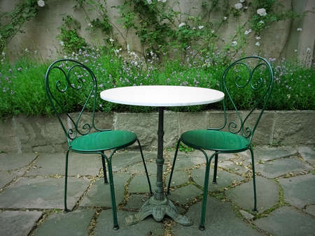 Chairs and table in a magic green summer garden.