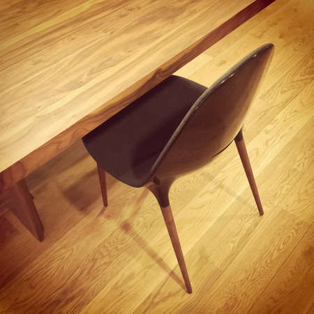 Black chair and wooden table, on hardwood floor.