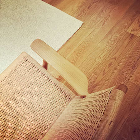 Home interior. Classic rattan chair on wooden floor. Stock Photo