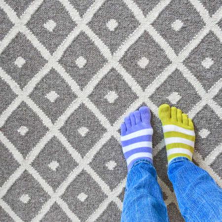 Grappige benen in slecht gecombineerde sokken op grijs tapijt.