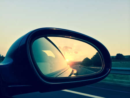 Sunset in a rear view mirror. Modern car on a highway. Imagens - 44444365