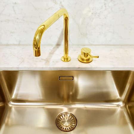 Aanrecht met gouden kraan, modern design. Stockfoto