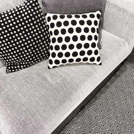 Black and white polka dot cushions on a sofa. Stylish modern furniture.