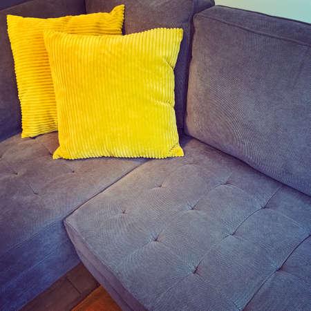 2 개의 밝은 노란색 쿠션으로 장식 된 편안한 코너 소파.