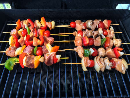 Outdoor grill with meat and vegetable skewers, ready to barbecue.