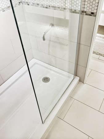 Nuevo cuarto de baño reformado con ducha y piso de cerámica. Foto de archivo