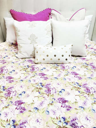 White and purple bed linen with floral design. Close-up of a bed.