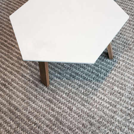 Modern white table on gray knitted rug. Scandinavian design. Фото со стока
