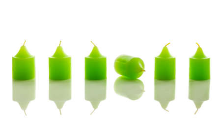 Row of green candles, with one laying down. With reflection, isolated on white background.