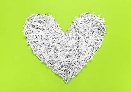 Heard made of shredded paper, on bright green background. Recycling concept.