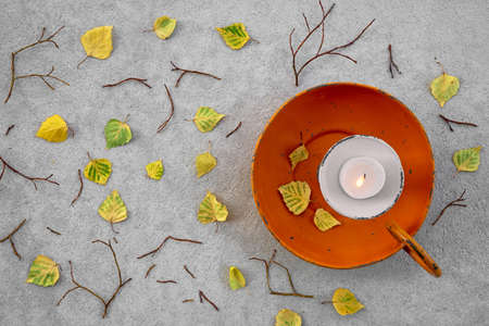 Autumn leaves and cozy candlelight on gray concrete background. Stock Photo