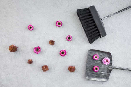 Sweeping away pink flowers with black brush and dustpan, on concrete floor background. Change of seasons concept.