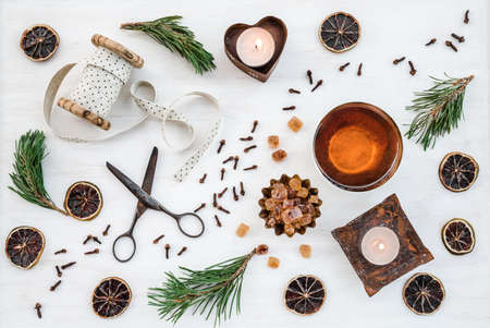 Traditional Christmas decor with candles, teacup and vintage items, on white background.