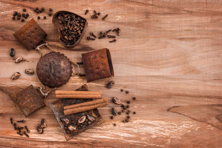 Spices and pine tree nuts in rusty metal plates, on wooden background with copy space.