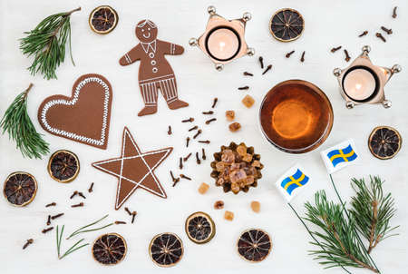 Swedish Christmas decor with flags, candles, teacup, ginger biscuits and spices. Stock Photo
