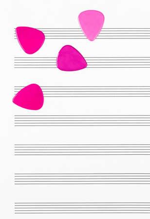 Vibrant crimson guitar picks on empty sheet music paper.