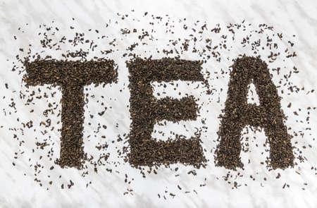 La palabra TEA escrita con hojas de té verde pólvora, sobre fondo de mármol. Foto de archivo