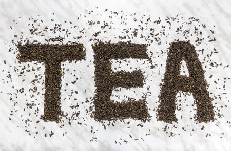 The word TEA written with Gunpowder green tea leaves, on marble background. Stok Fotoğraf