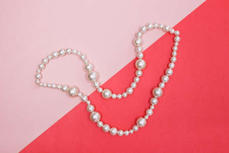Shiny pearl necklace on pink background, looking like a smile. Stock Photo