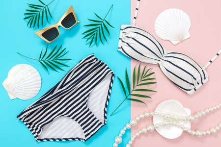 Summer holidays flat lay on blue and pink background. Bikini, sunglasses, palm leaves, pearl necklace and seashells. Banco de Imagens