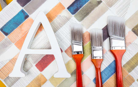 Three paint brushes and letter A on artistic watercolor background. Stockfoto