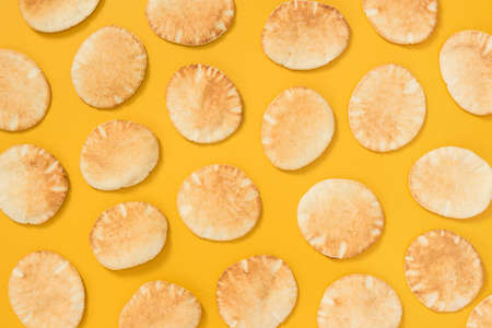 Lots of freshly baked mini pita bread on bright yellow background.