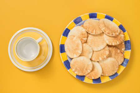 Teacup and colorful plate with mini pita bread on bright yellow background.