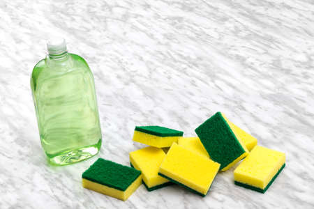 Green and yellow sponges and dishwashing liquid and on marble kitchen countertop. Zdjęcie Seryjne