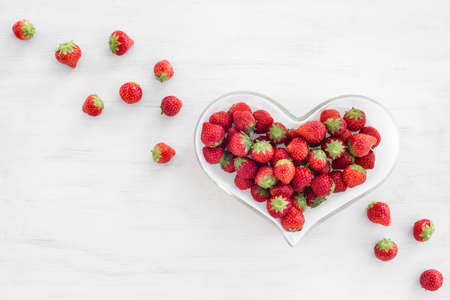 Strawberries in a heart-shaped bowl, on white wooden background. Stock fotó