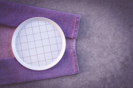 Checked white plate and purple tablecloth, on dark concrete background with copy space.