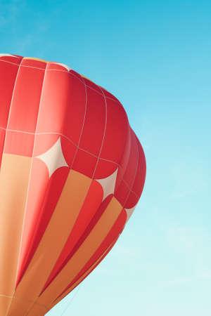 Close-up of  vivid orange hot air balloon in the blue sky. Archivio Fotografico