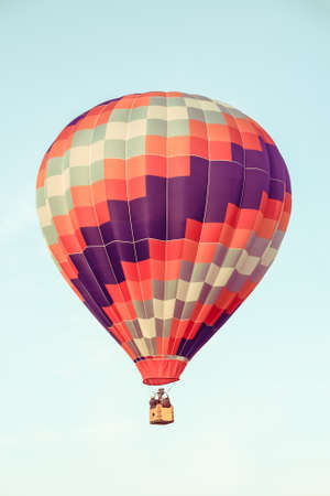 Red and purple hot air balloon floating in the clear sky. Stock Photo
