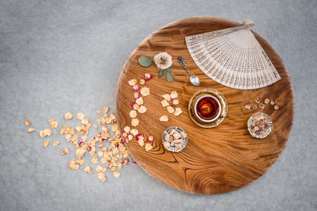 Tea and sugar on a round wooden table decorated with rose petals and fan. Stock Photo