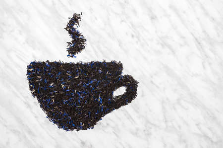Teacup with steam made of black Earl gray tea leaves, on marble background with copy space.