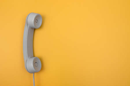 Classic gray telephone receiver on bright yellow background with copy space. 写真素材
