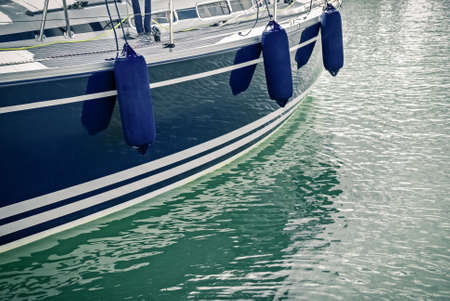 Side of a blue motorboat with fenders reflecting in calm green water. Stock Photo