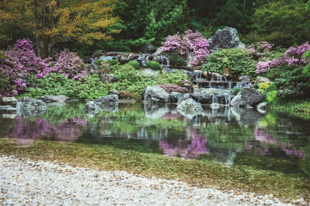 Pond with water cascades in a blooming Japanese garden.