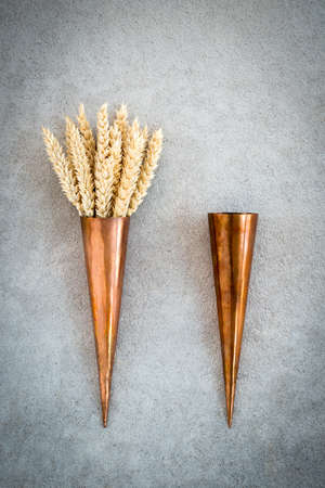 Vintage copper cones and wheat ears, on concrete background.
