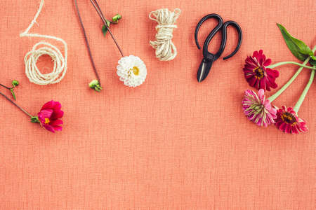 Florist workspace. Fresh flowers, scissors and twine on peach colored canvas background with copy space.