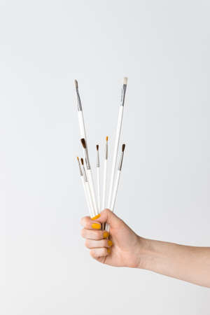 Hand holding white paintbrushes, on neutral background with copy space.